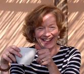 Katharina prenant son café sur la terrasse de Duna Grande, une villa en bord de mer pied dans l'eau